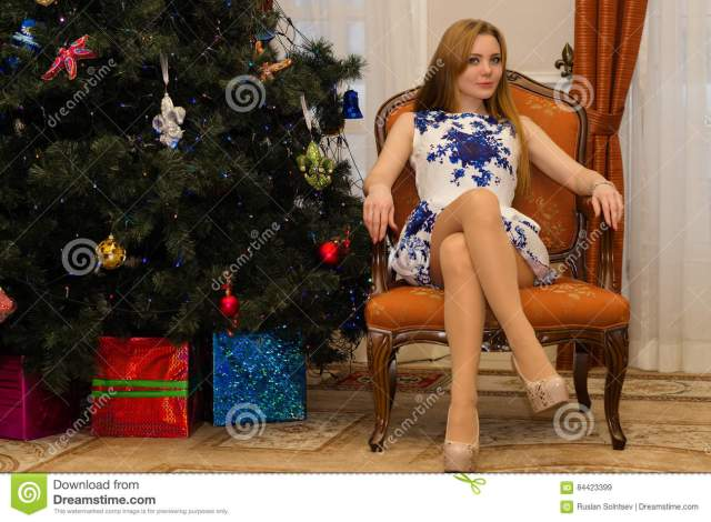 Charming Woman Sitting On Chair With Legs Crossed