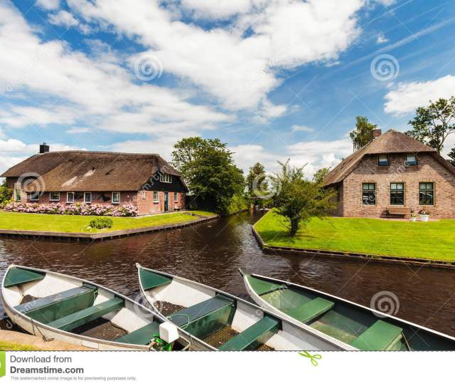 Small Canal Cruise Boats In Front Of Old Houses In The Dutch Village Of Giethoorn