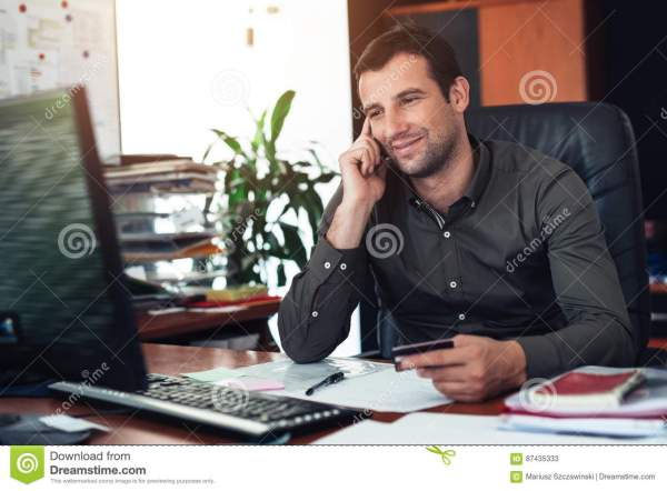 Smiling Businessman Paying Bills Over The Phone In An ...