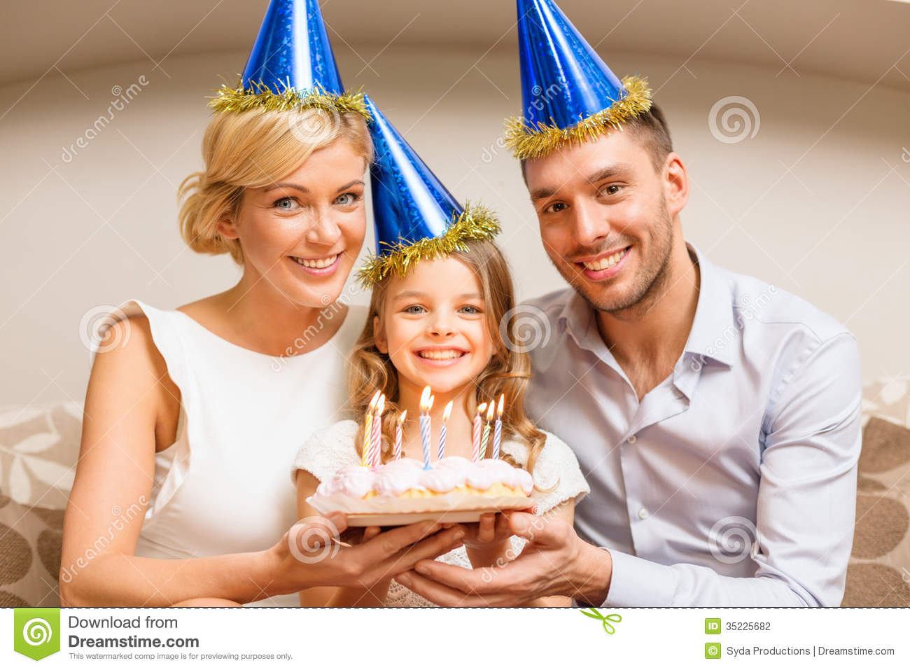 Smiling Family In Blue Hats With Cake Stock Photography