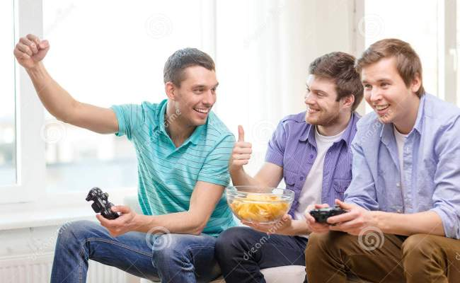 Smiling Friends Playing Video Games At Home Stock Photo