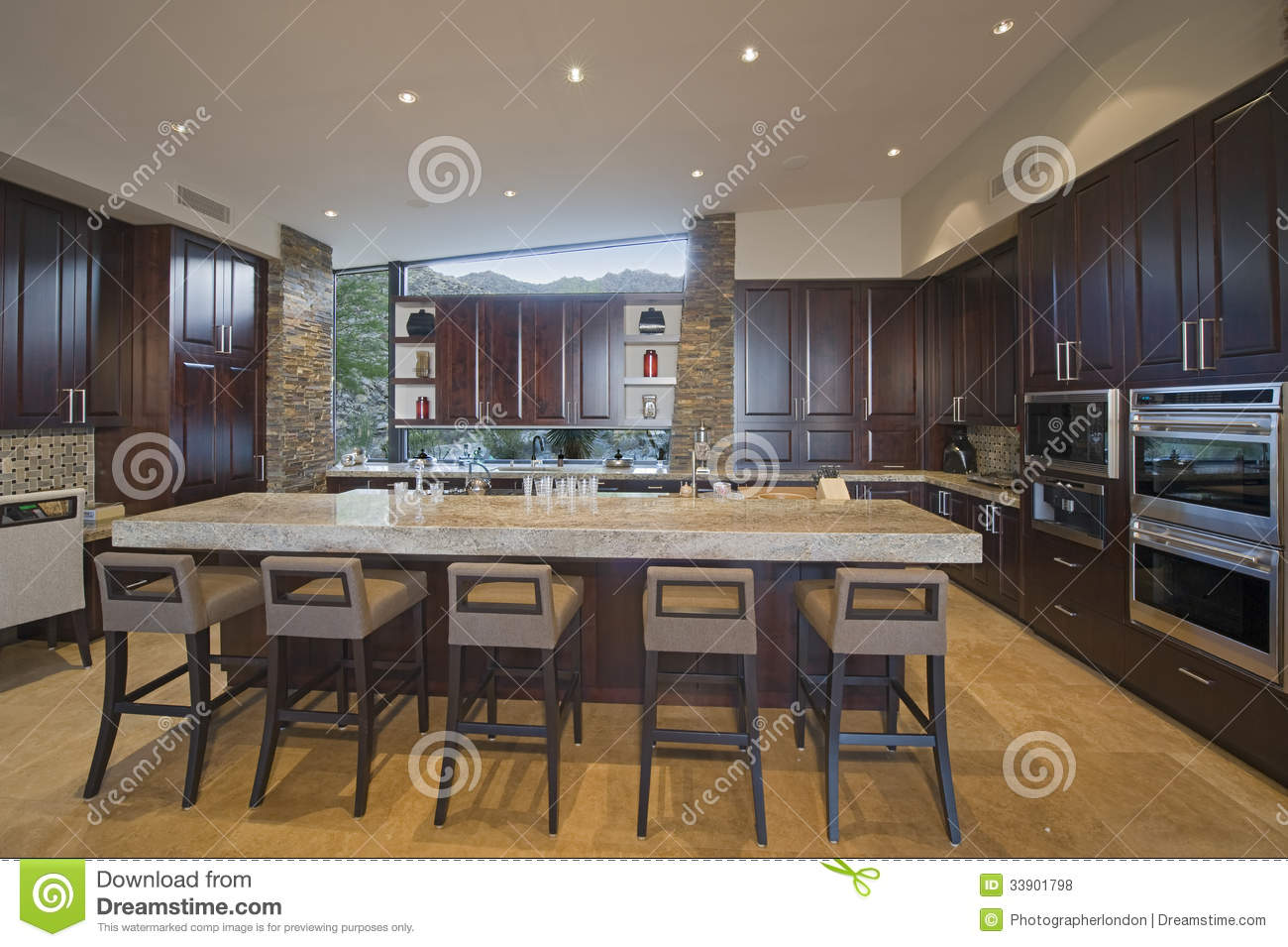 Spacious Kitchen With Stools At Island In House Stock
