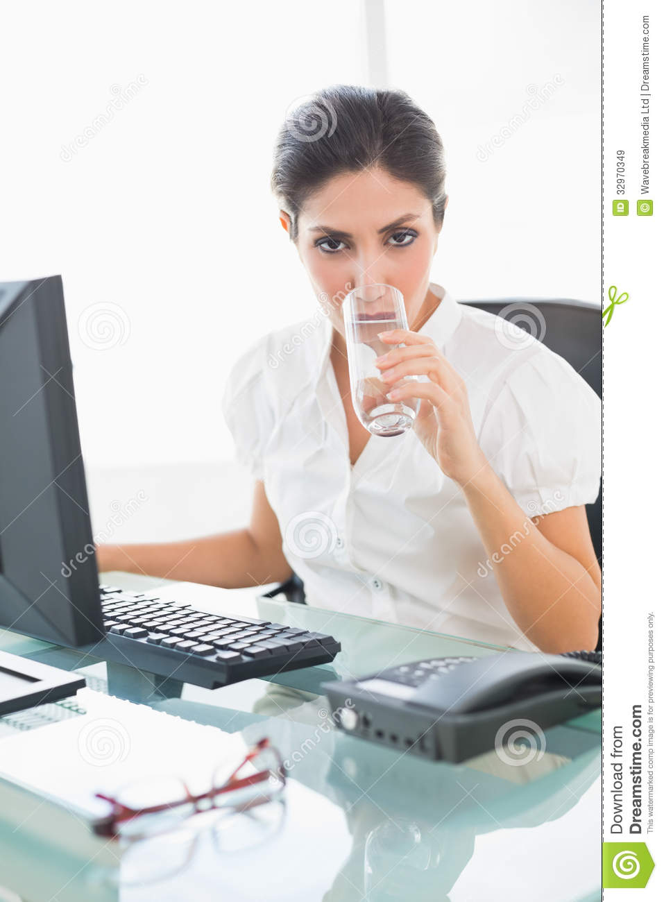 Stern Businesswoman Drinking A Glass Of Water At Her Desk