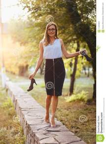 Stylish Young Woman Walking Barefoot And Holding Shoes In