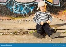 Boy Sitting On Sidewalk