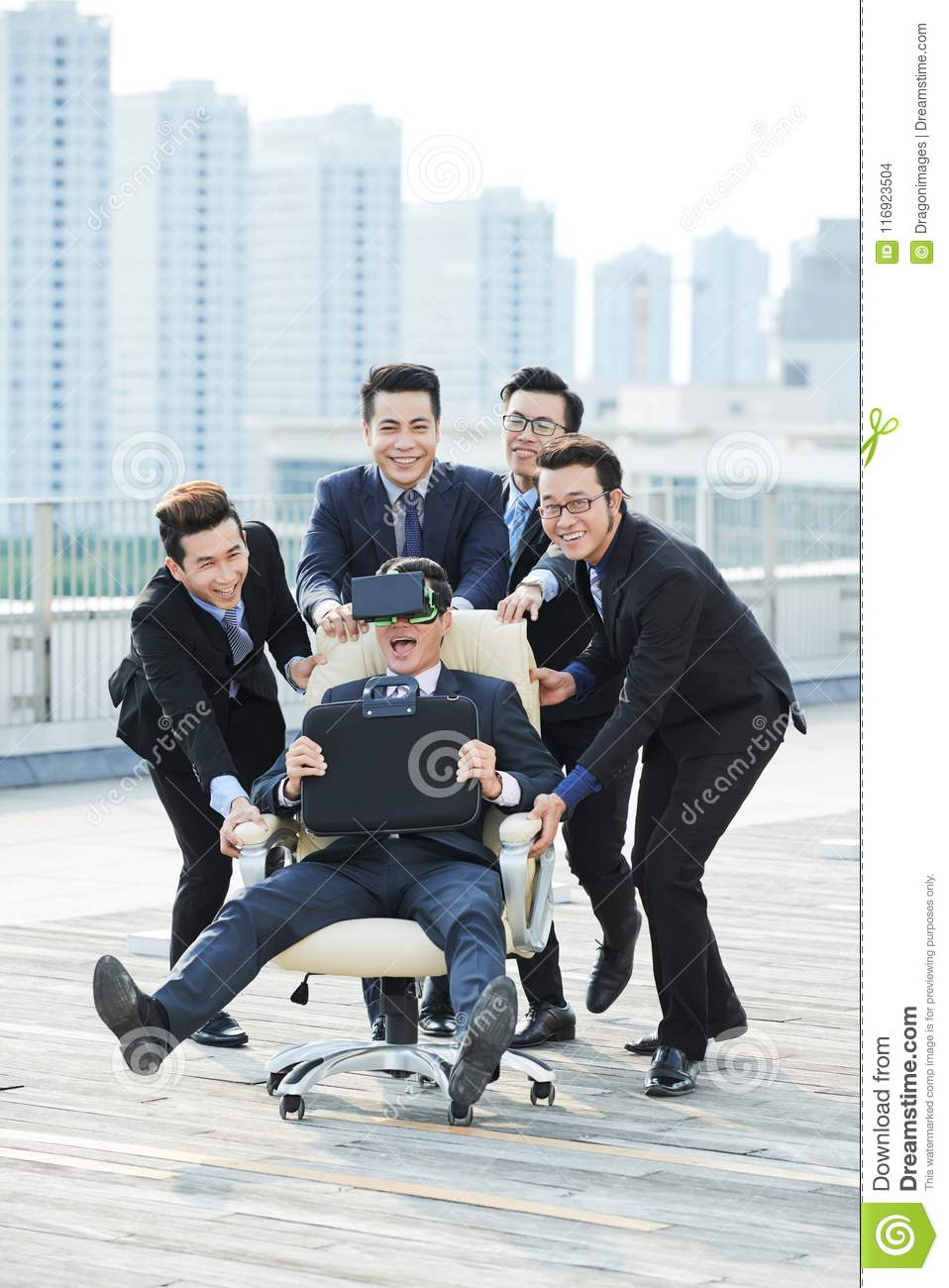 swivel chair vr wicker back chairs playing fool at spacious terrace stock photo image of happy surprised businessman wearing headset sitting on with briefcase in hands while his cheerful colleagues pushing it along