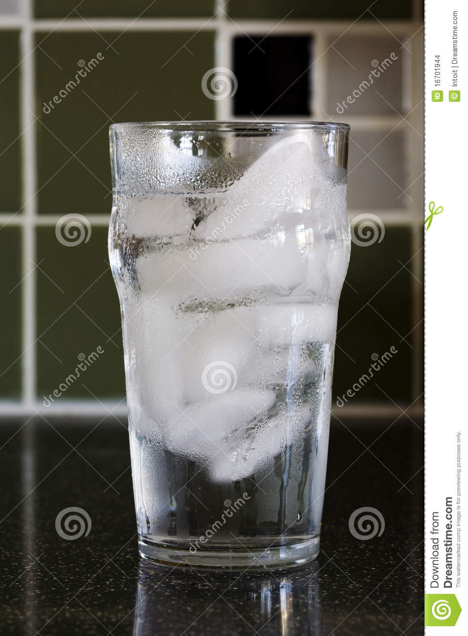 Sweating Class Of Cold Water And Ice Cubes Stock Images