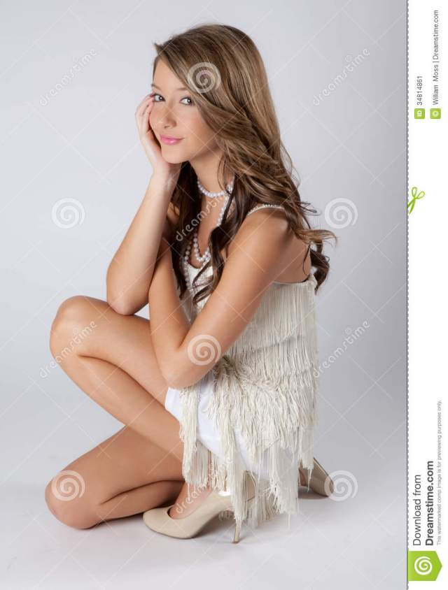 An Image Of A Pretty Smiling Teenager In A White Fringed Dress And Pearls