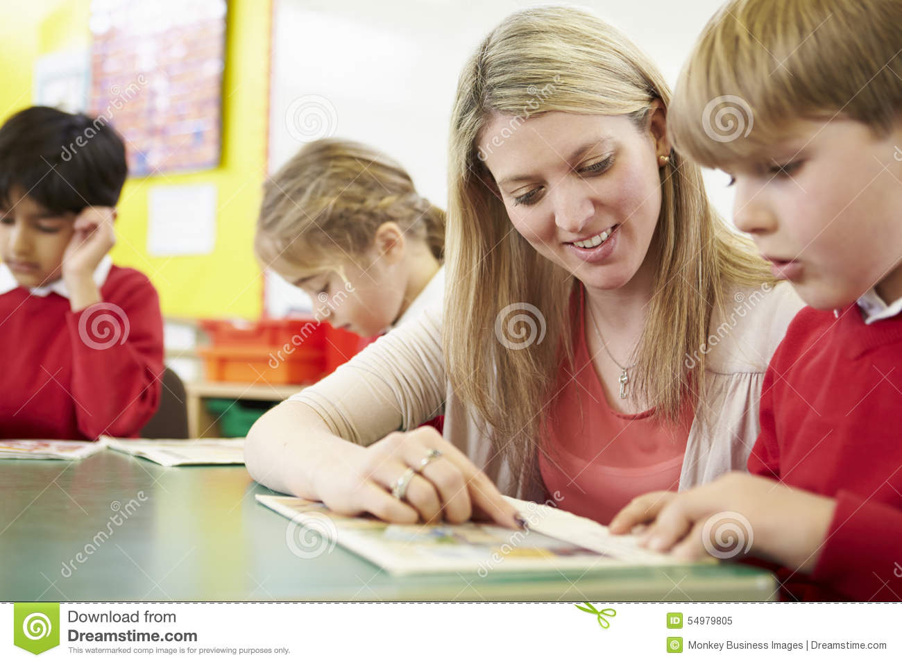 Teacher Helping Male Pupil With Reading At Desk Stock