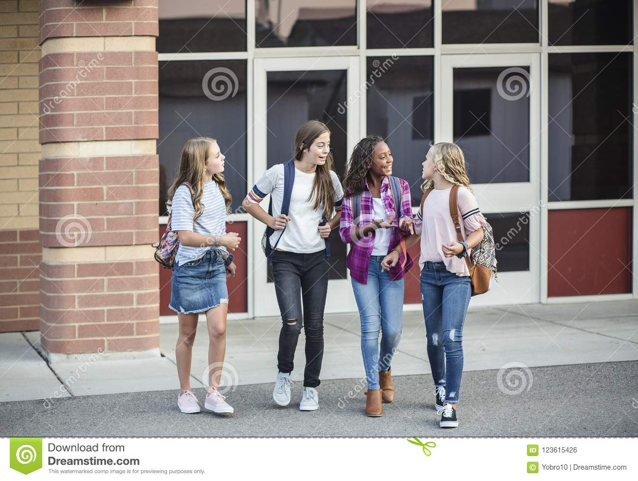 Teen Girls Leaving School Talking And Walking Together