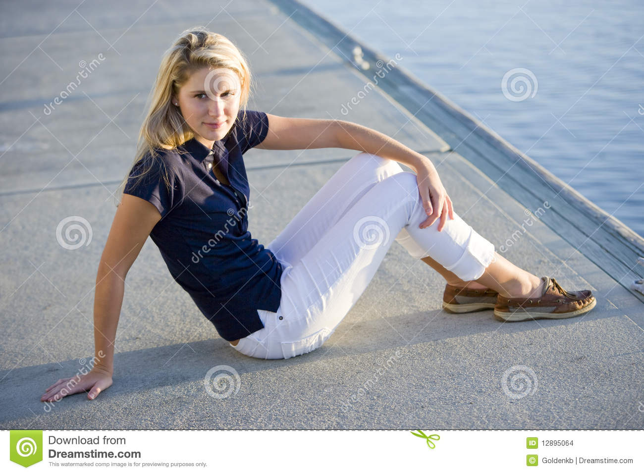 Teenage Girl Sitting On Dock By Water Stock Photo  Image