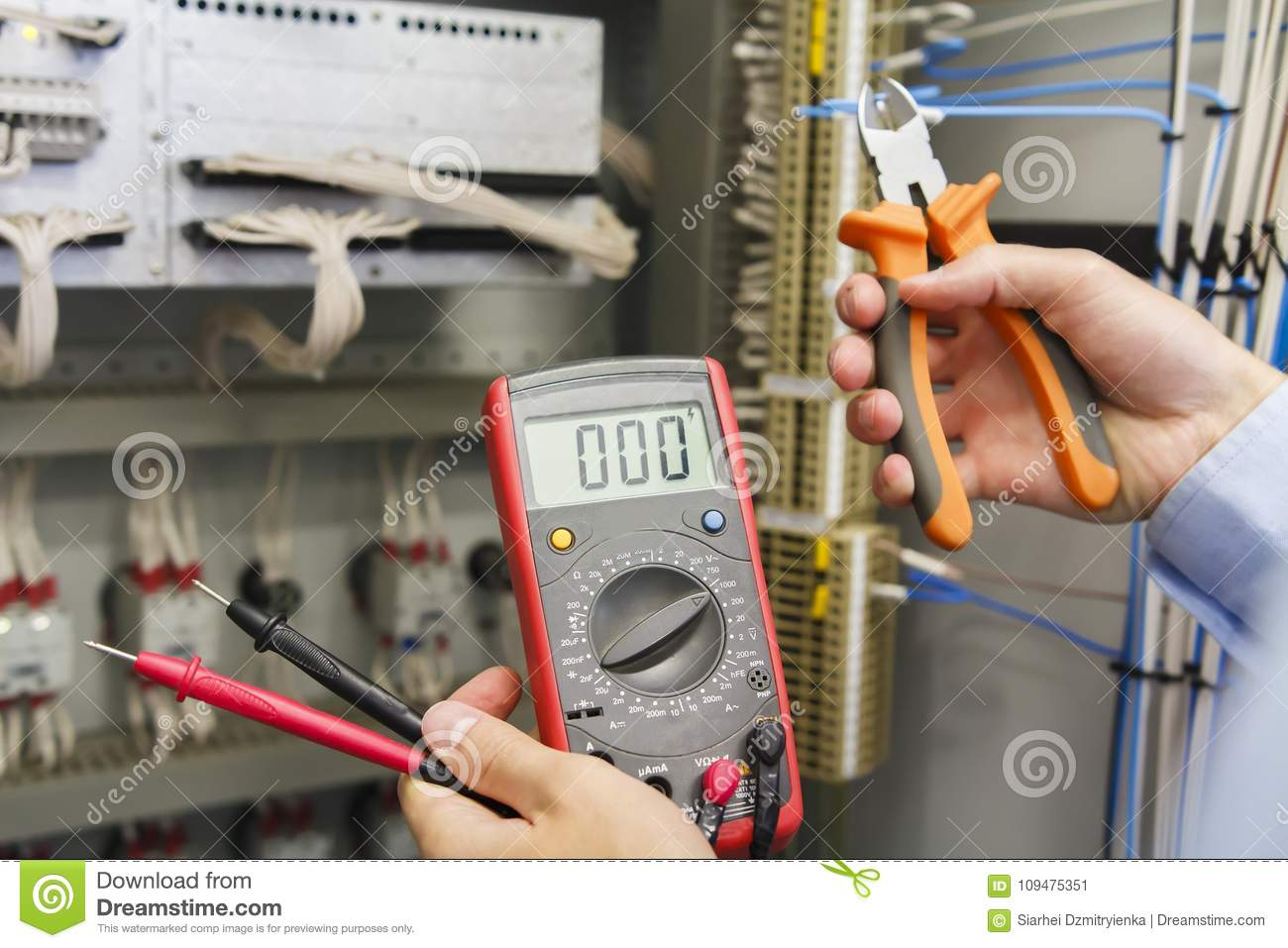 hight resolution of tester and wire cutters in hands of electrician against electric control panel of automation equipment