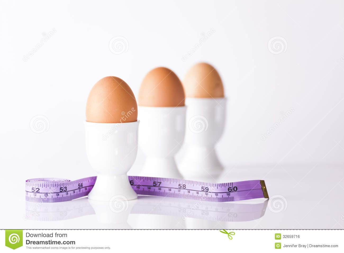 three boiled eggs measuring tape white egg cups signifying weight loss 32659716