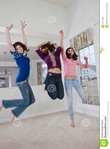Three Teenage Girls Leaping And Dancing Home Stock