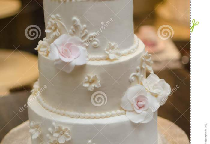 Three Tier Wedding Cake With Cream Roses And Decorations Stock Image