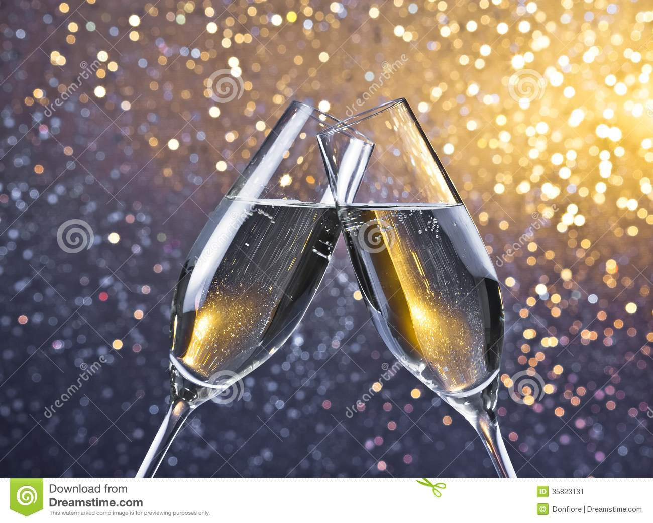 Two Champagne Flutes With Golden Bubbles On Light Bokeh