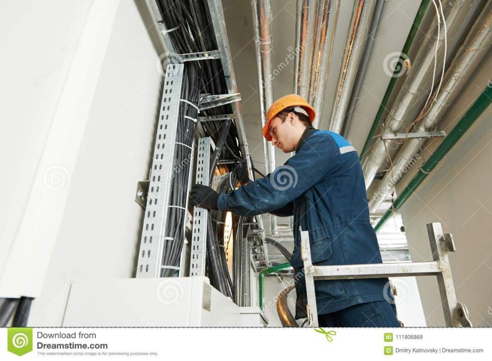 medium resolution of two electrician builder engineers workers installing industrial cable into fuse box