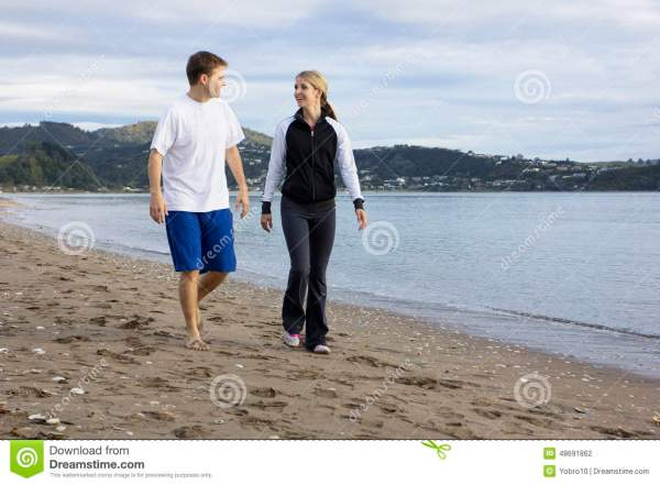 Two Friends Talking And Walking Beach Stock - 48691862
