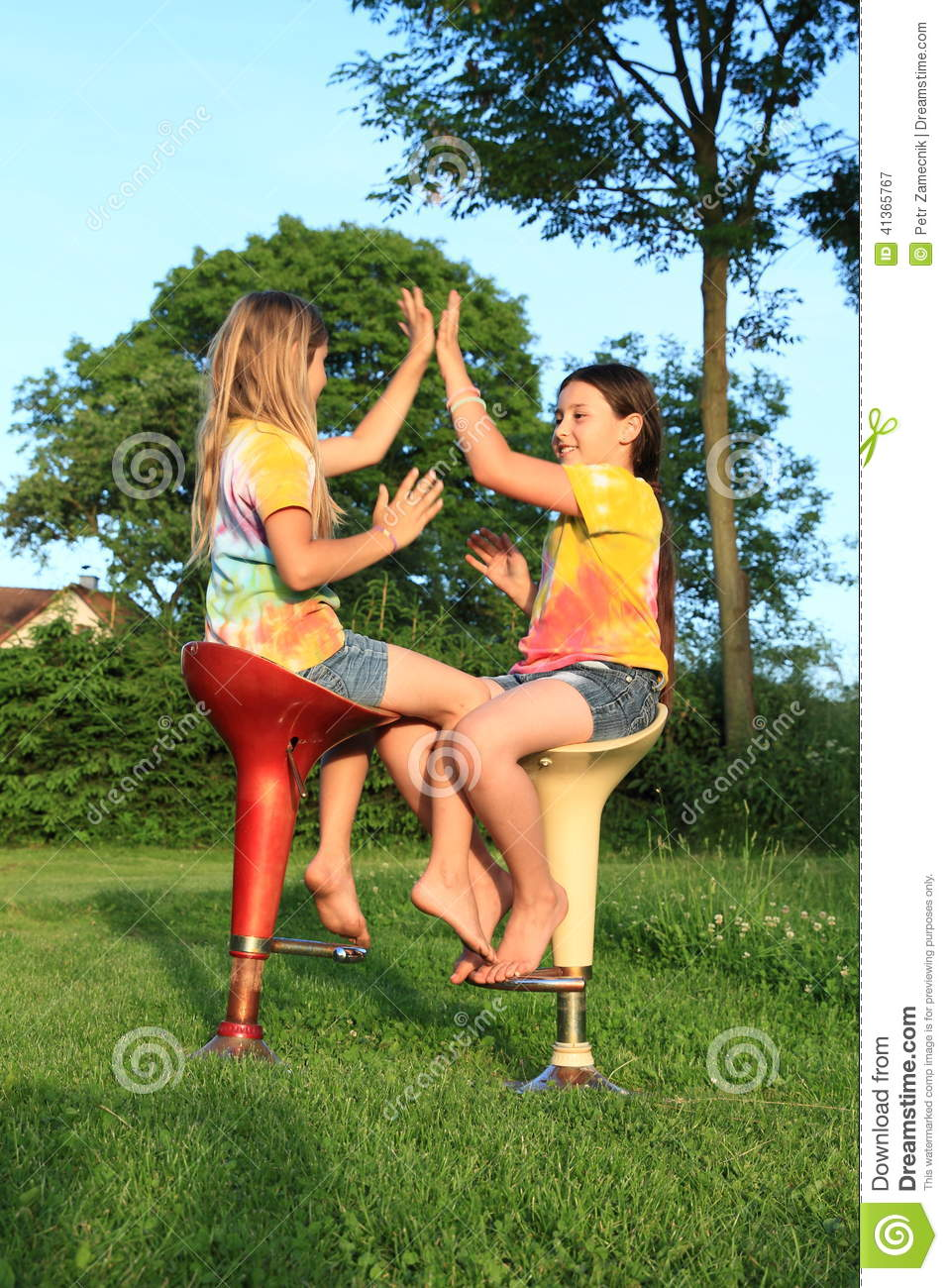 Two Girls Playing Game While Sitting On Bar Chairs Stock