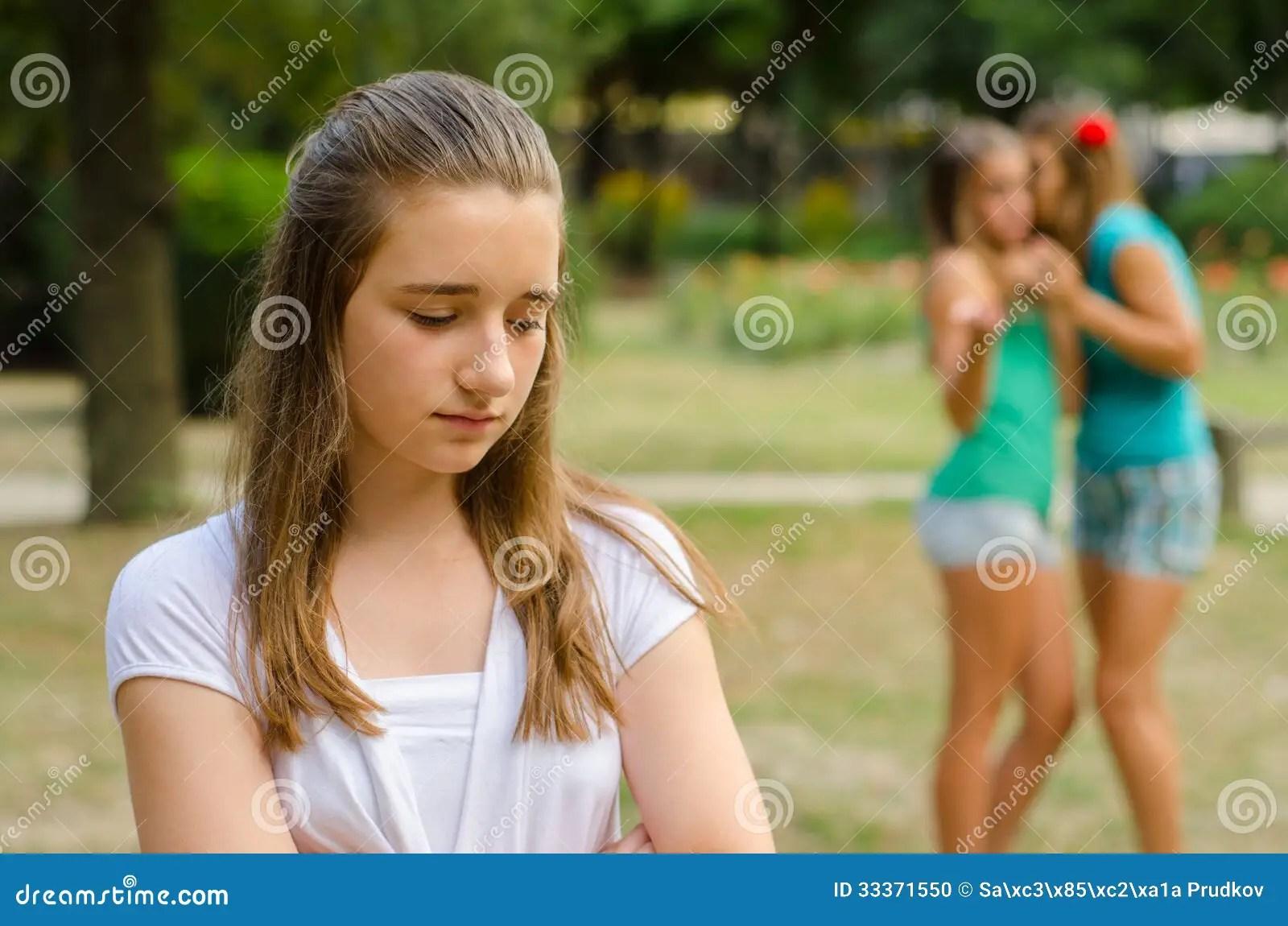 Two Teenage Girls Making Fun Of The Third Stock Photo