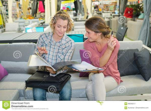 Two Woman Friends Sofa Reading Brochure Magazine