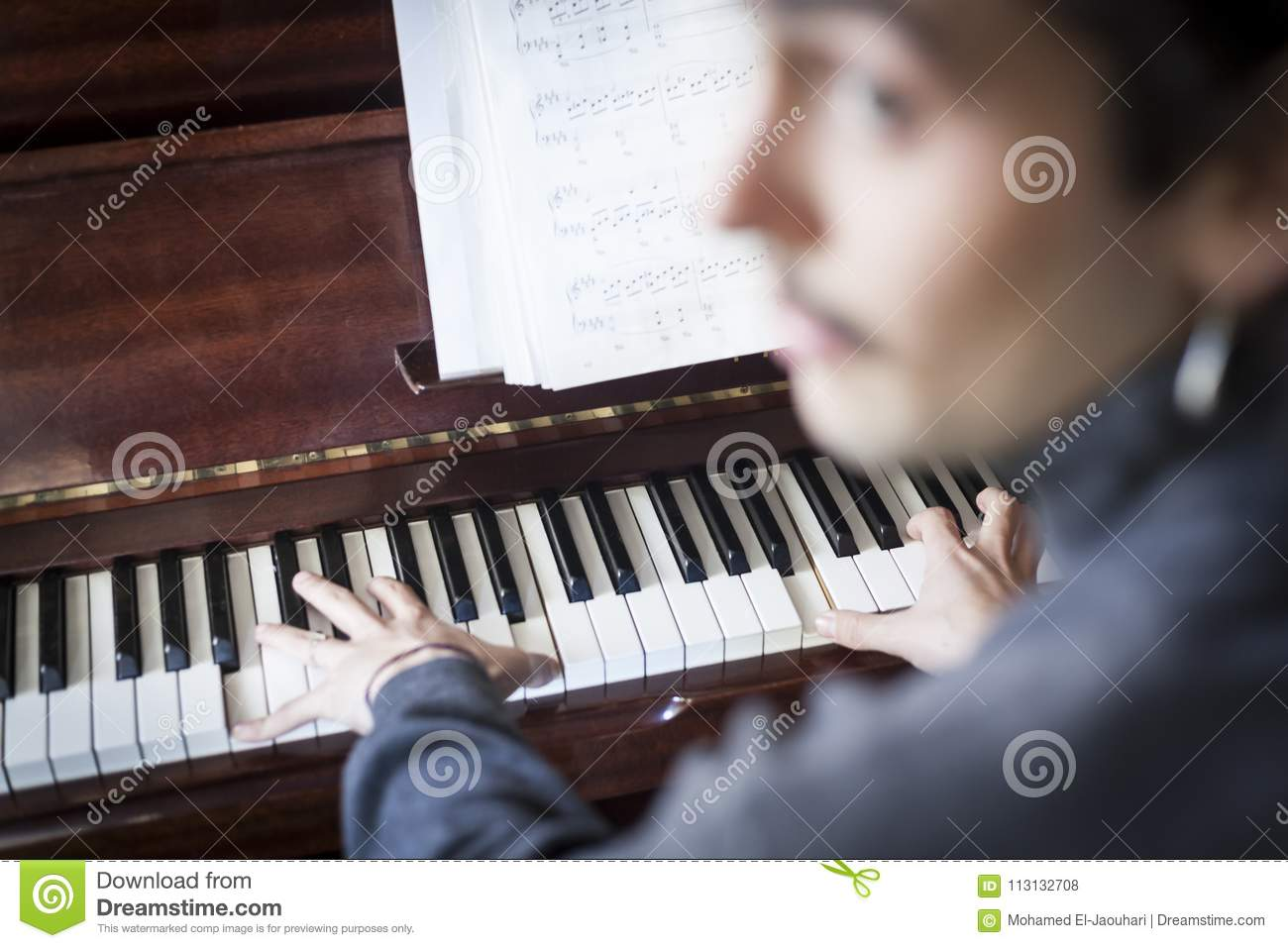 Unfocused Musician Playing Piano With Music Sheets Stock Photo