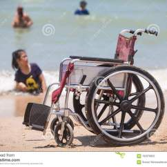 Wheelchair Fight Outdoor Rocking Chairs Walmart On Beach With Disabled Swimming In Sea Stock Photo