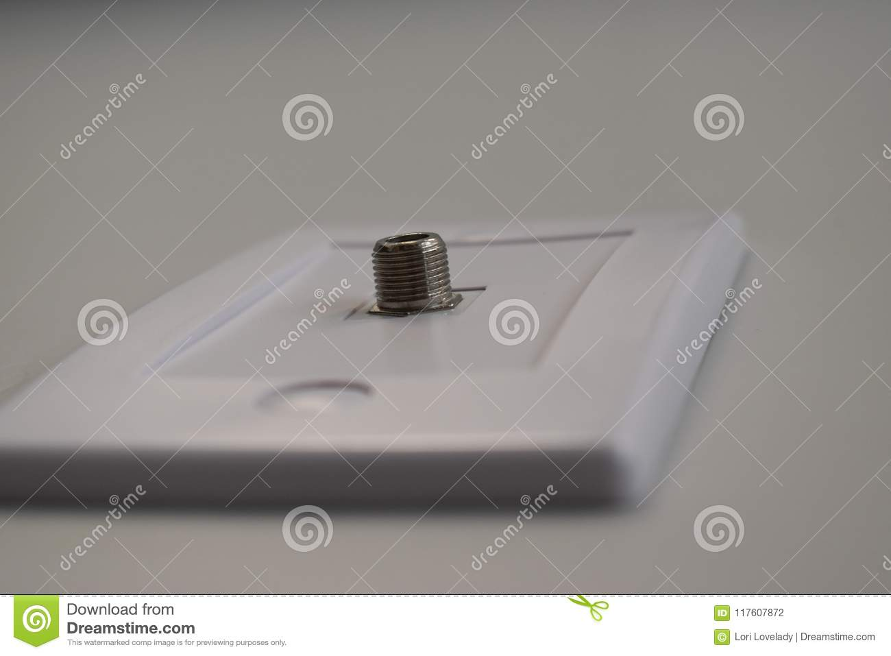 hight resolution of a white face plate containing a silver cable jack connected into the wall