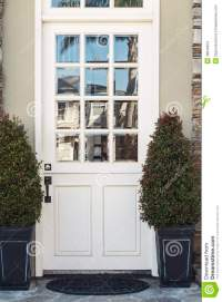 White Front Door To Modern Home Flanked By Plants Stock