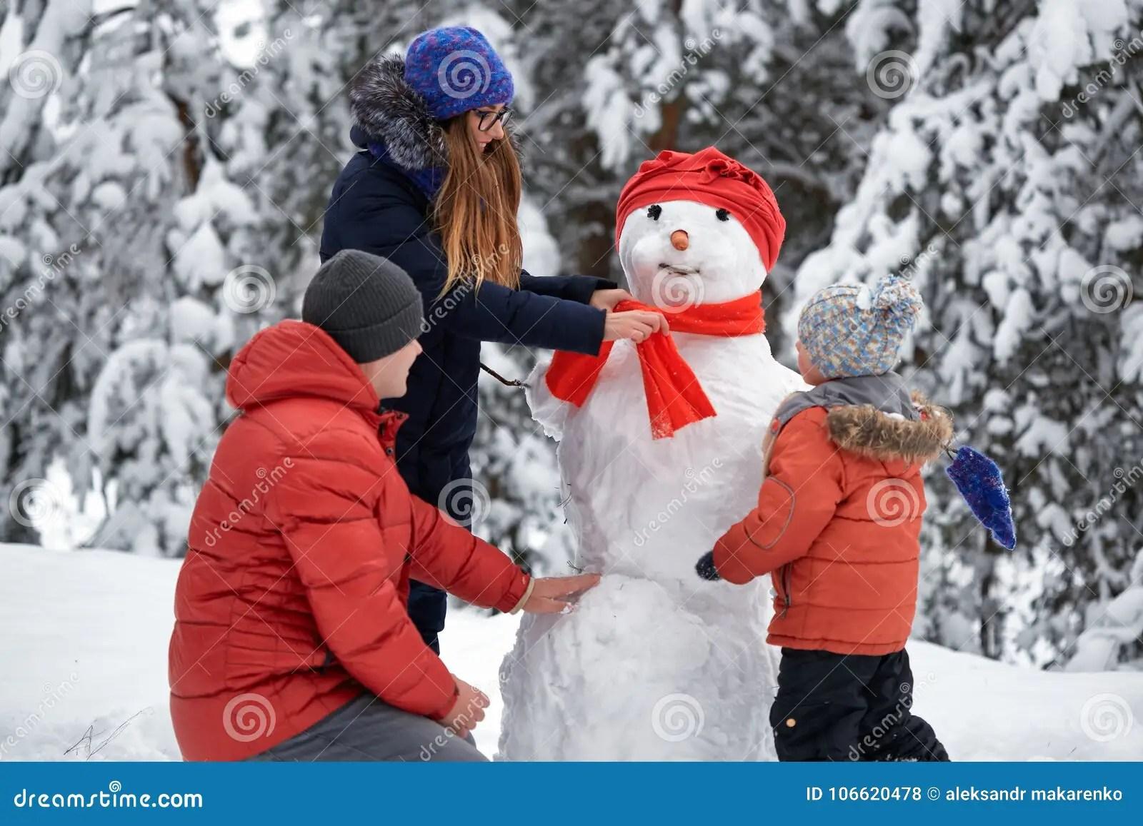 Winter Fun A Girl A Man And A Boy Making A Snowman
