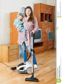Woman Cleaning Living Room With Vacuum Cleaner Stock Photo