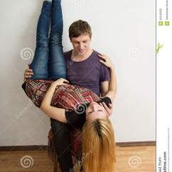 Chair Upside Down On Wall Hanging For Back The Woman Is Lying Man S Knees Stock Photo Image Of A Couple Sitting Women Her Legs Are Leaning