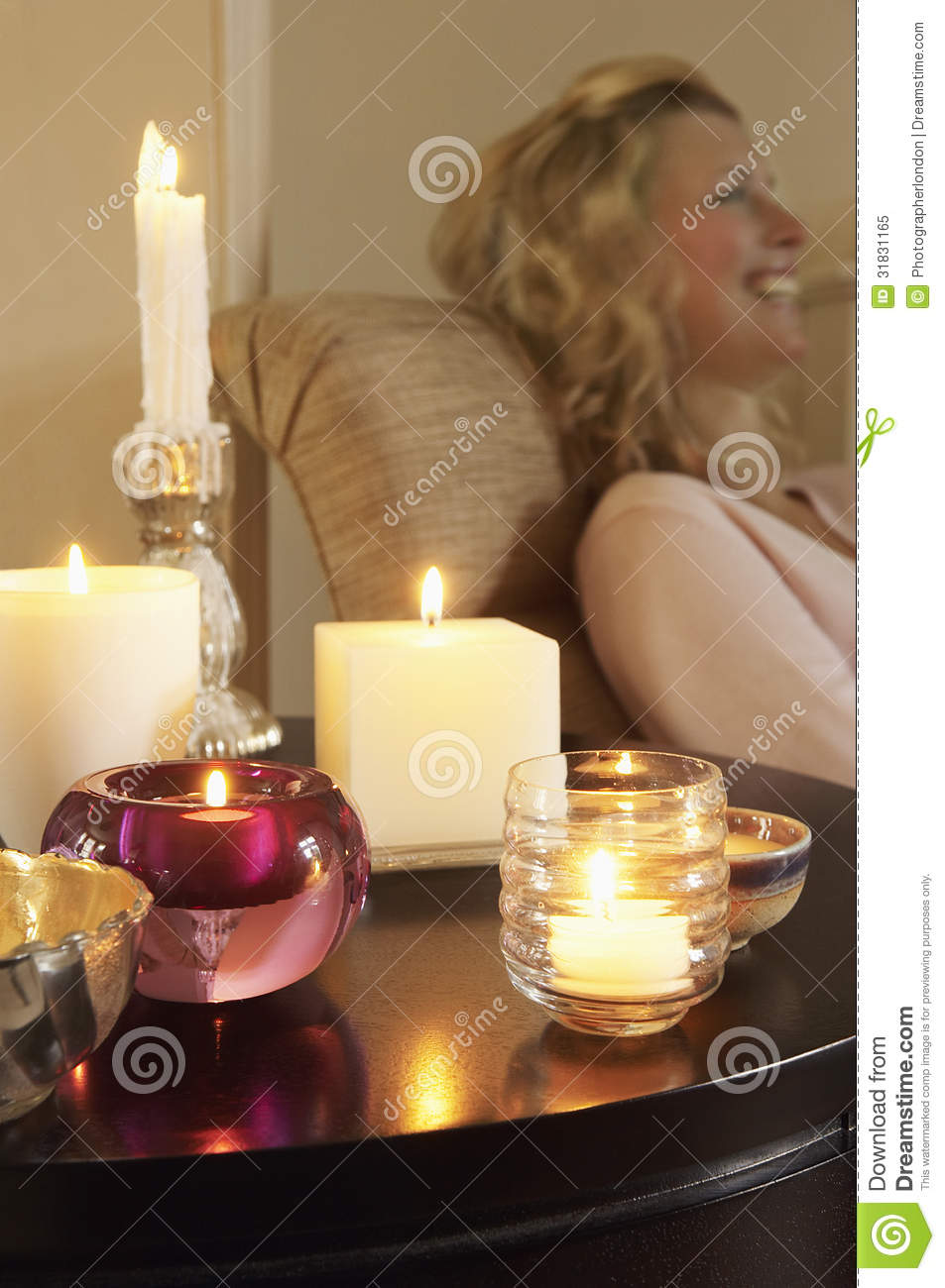 Woman Relaxing By Table With Lit Candles Stock Image
