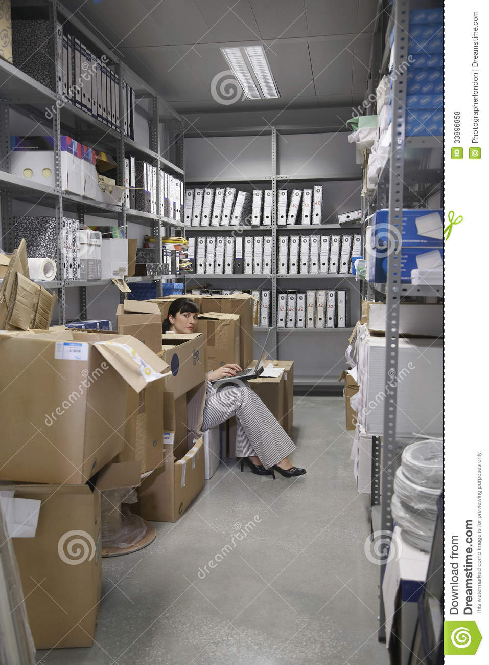 Woman Using Laptop In Office Storage Room Royalty Free