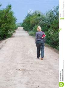Woman Walking Barefoot On Dirt Road
