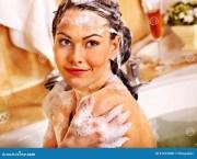 woman washing hair in bubble bath