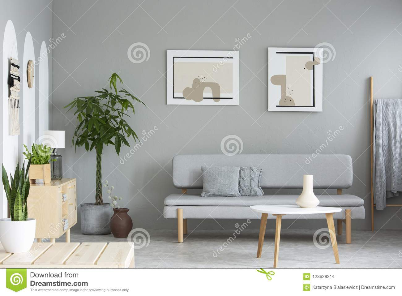 Wooden Table In Front Of Grey Sofa In Simple Living Room