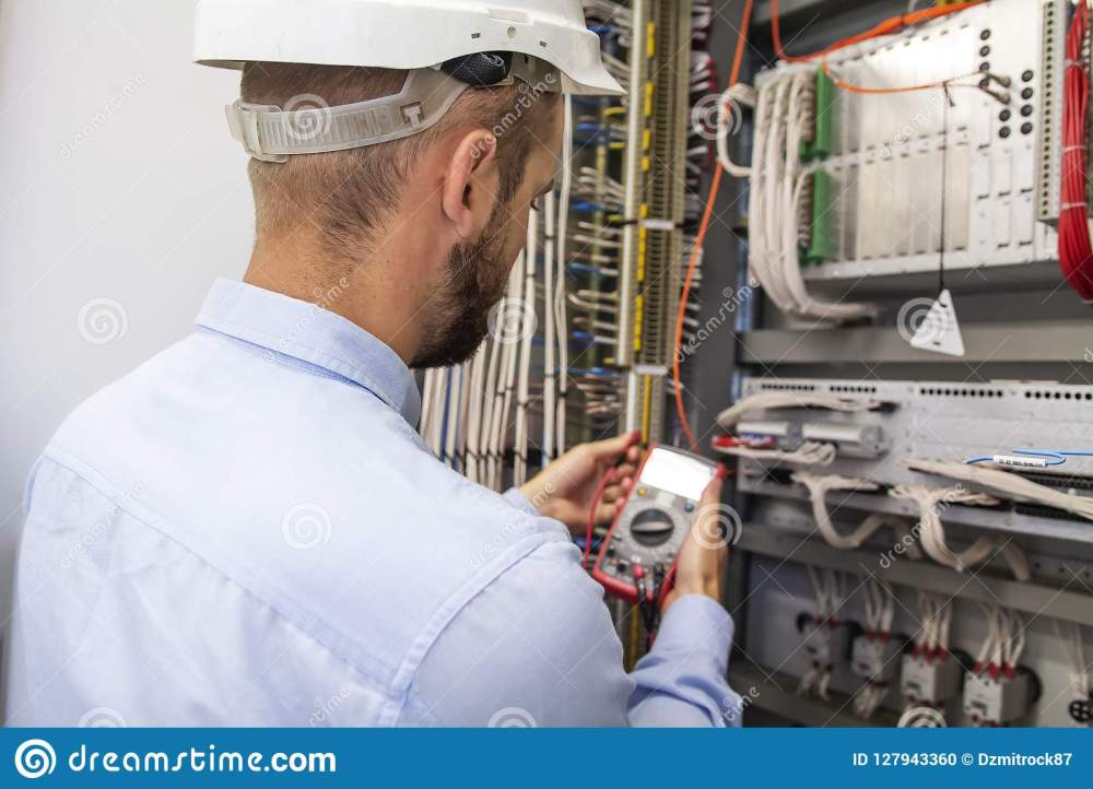 medium resolution of young adult electrician builder engineer inspecting electricyoung adult electrician builder engineer inspecting electric equipment in distribution
