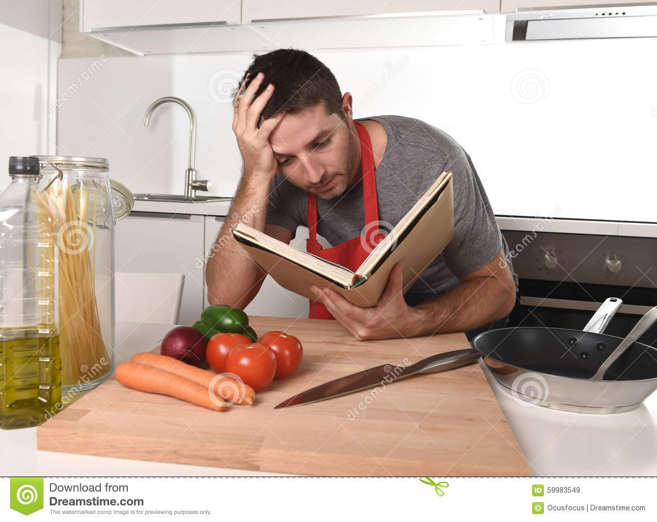 Young Attractive Man At Home Kitchen Reading Recipe Book