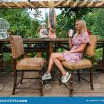 Young Beautiful Blonde Woman In A Pink Dress Sits With A Cup Of Coffee In Her Hands In A Cafe Or Restaurant In Vintage Style In Stock Image Image Of Cheerful