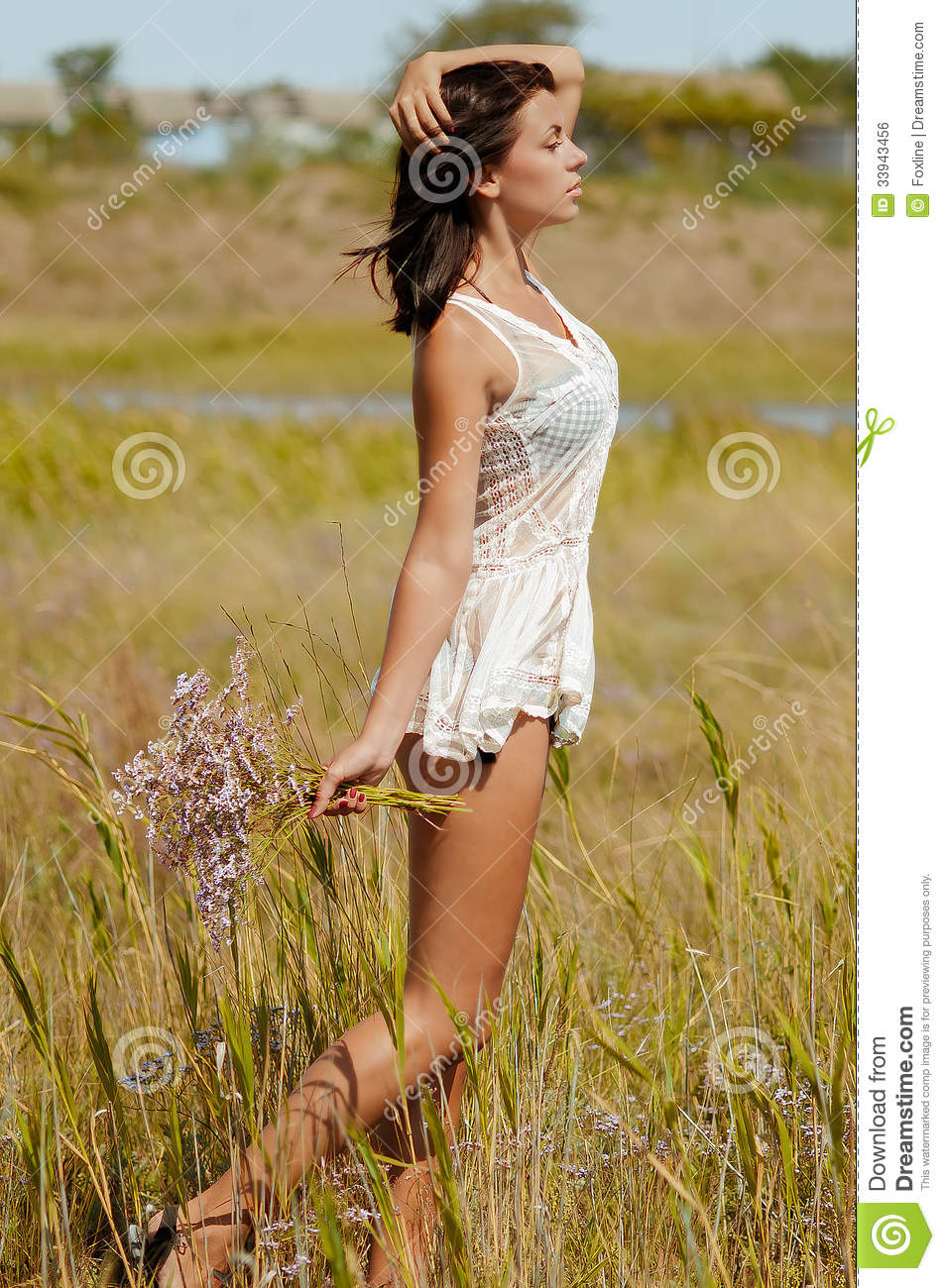 Young Beautiful Girl In A Field With Flowers In White