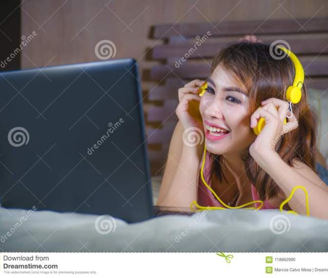 Young Beautiful And Happy Girl Watching On Line Internet Movie O