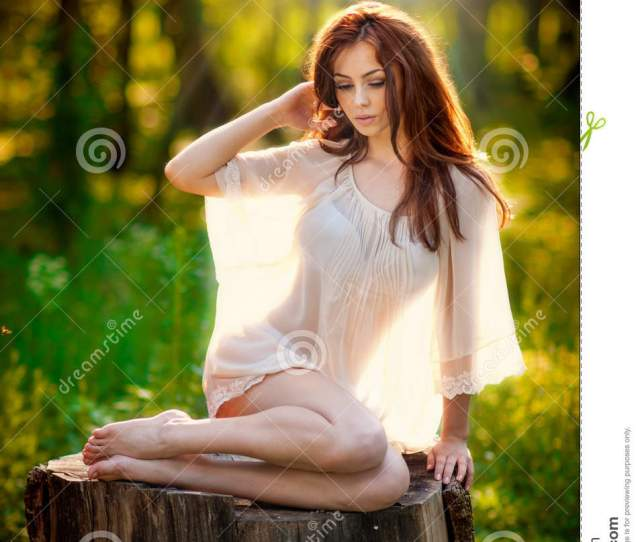 Young Beautiful Red Hair Woman Wearing A Transparent White Blouse Posing On A Stump In A Green Forest Fashionable Attractive Girl Sitting On Hub In Sunny