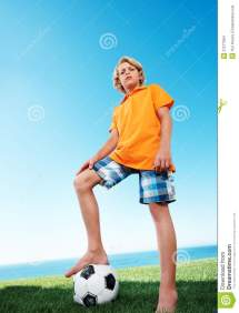 Young Boy Standing Confidently With Football Under Stock