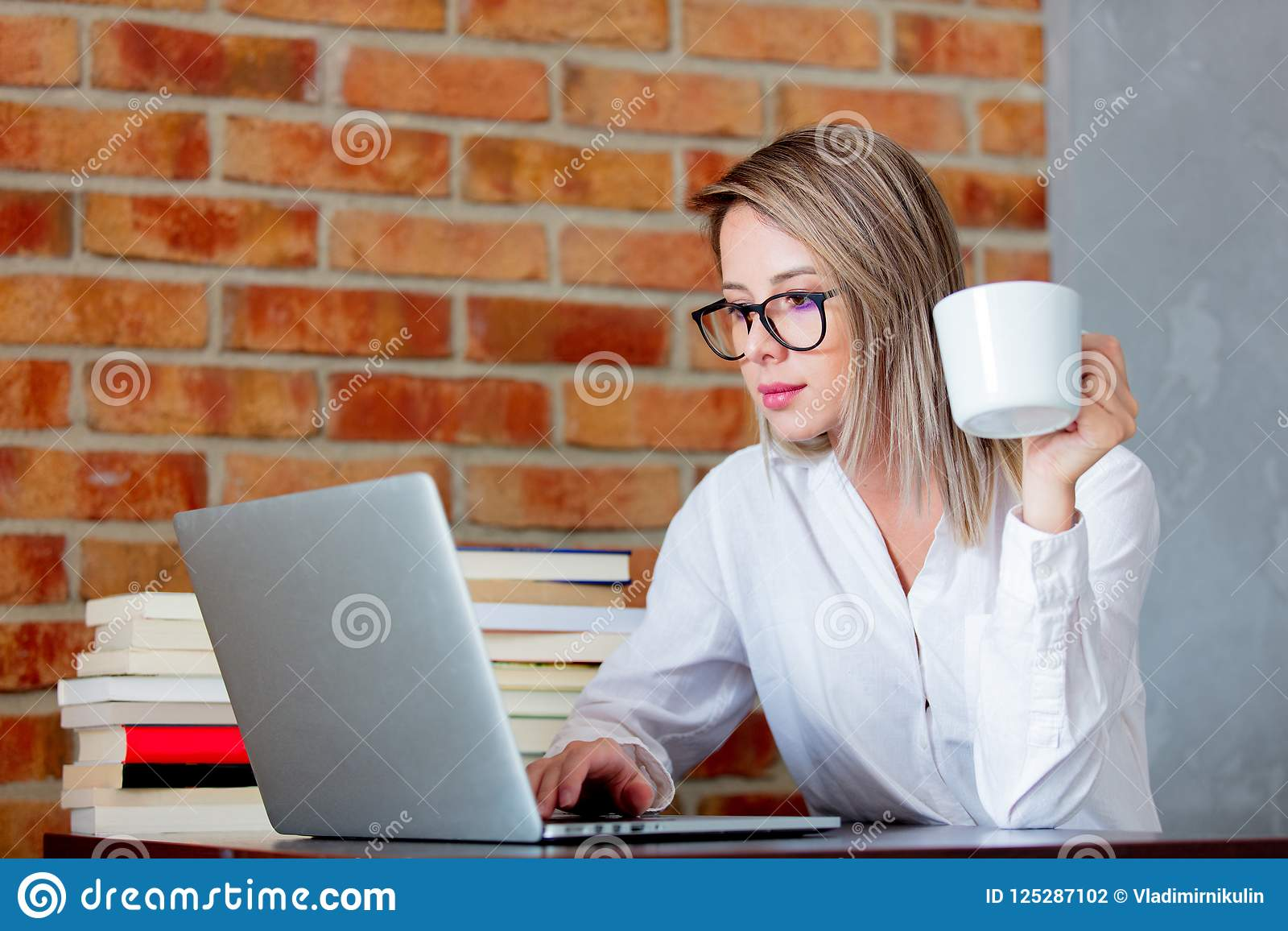 Woman On Working Place Holding A Cup Of Hot Drink Stock ...