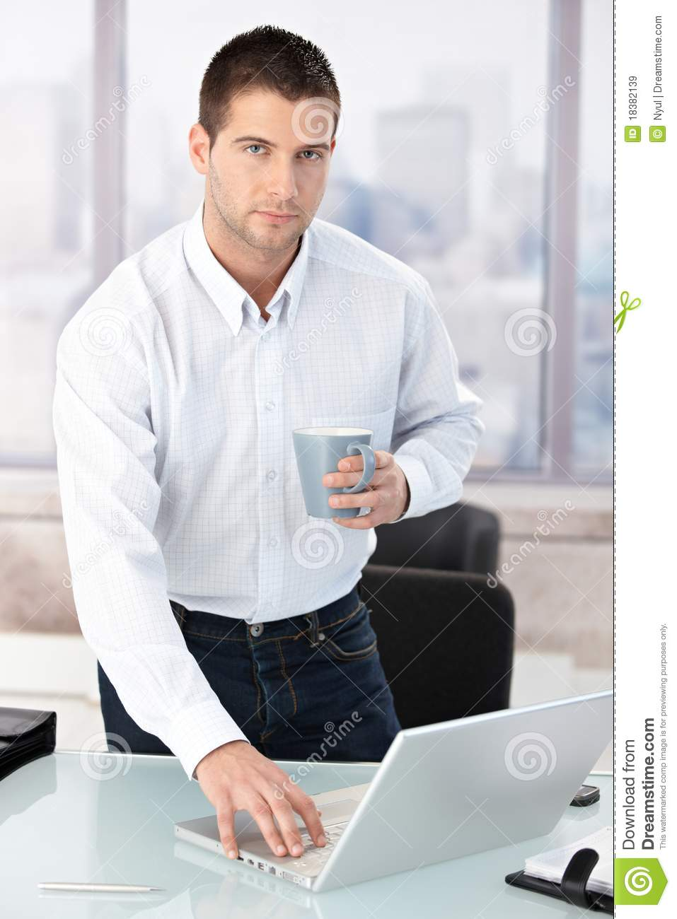 Young Casual Office Worker Using Laptop In Office Royalty