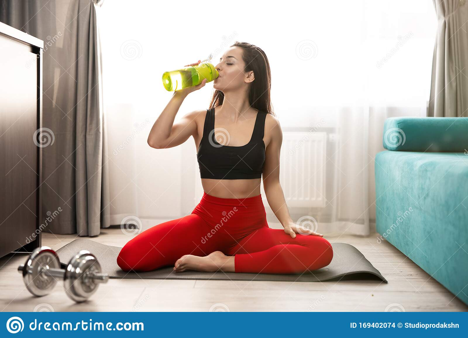 Young Fit Woman In Sportwear Drinks Water While Doing