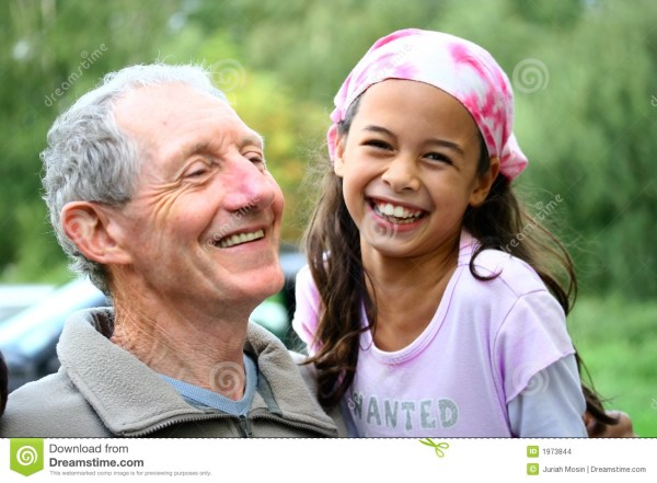 Young Girl Sharing Joke With Grandfather Stock