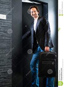 Man Entering Hotel with Suitcase