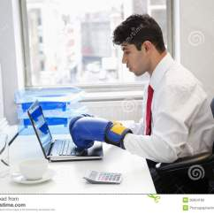 Office Side Chair Margaritaville Beach Chairs Young Indian Businessman Wearing Boxing Gloves While Using Laptop At Desk Royalty Free ...
